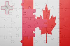 Puzzle with the national flag of canada and malta. Concept Royalty Free Stock Photo