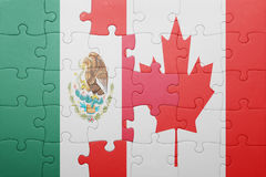 Puzzle with the national flag of canada and mexico. Concept royalty free stock photography