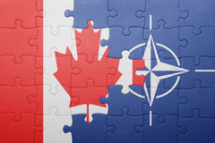 Puzzle with the national flag of canada and nato Stock Photography