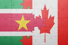 Puzzle with the national flag of canada and suriname. Concept Royalty Free Stock Images