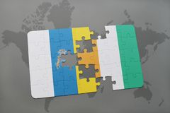 Puzzle with the national flag of canary islands and cote divoire on a world map background. 3D illustration Royalty Free Stock Photos