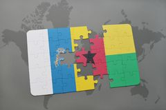 Puzzle with the national flag of canary islands and guinea bissau on a world map background. 3D illustration Stock Images