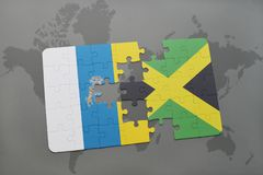 Puzzle with the national flag of canary islands and jamaica on a world map background. 3D illustration Stock Photography
