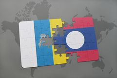 Puzzle with the national flag of canary islands and laos on a world map background. 3D illustration Stock Images