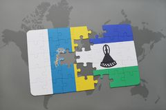Puzzle with the national flag of canary islands and lesotho on a world map background. 3D illustration Stock Image