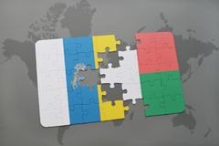 Puzzle with the national flag of canary islands and madagascar on a world map background. 3D illustration Royalty Free Stock Images