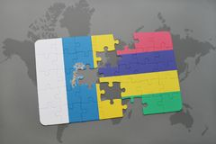 Puzzle with the national flag of canary islands and mauritius on a world map background. 3D illustration Royalty Free Stock Photos