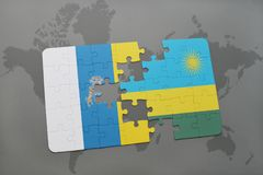Puzzle with the national flag of canary islands and rwanda on a world map background. 3D illustration Royalty Free Stock Photo
