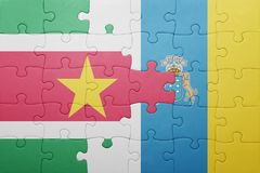 Puzzle with the national flag of canary islands and suriname. Concept Royalty Free Stock Photo