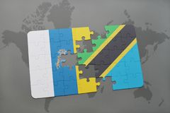Puzzle with the national flag of canary islands and tanzania on a world map background. 3D illustration Stock Photos