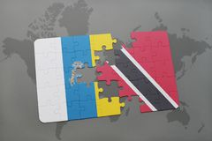 Puzzle with the national flag of canary islands and trinidad and tobago on a world map background. 3D illustration Royalty Free Stock Images