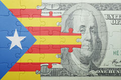 Puzzle with the national flag of catalonia and dollar banknote. Concept Stock Photography