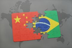 Puzzle with the national flag of china and brazil on a world map background. 3D illustration royalty free stock photography