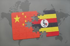 Puzzle with the national flag of china and uganda on a world map background. 3D illustration royalty free stock photography