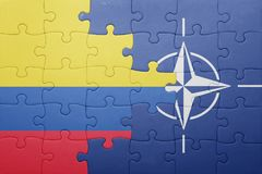 Puzzle with the national flag of colombia and nato Royalty Free Stock Image