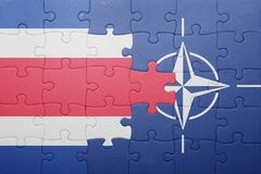Puzzle with the national flag of costa rica and nato. Concept royalty free stock photography