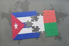 Puzzle with the national flag of cuba and madagascar on a world map background. 3D illustration stock photos