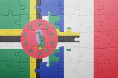 Puzzle with the national flag of dominica and france. Concept royalty free stock images