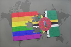 Puzzle with the national flag of dominica and gay rainbow flag on a world map background. 3D illustration stock images