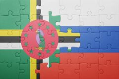 Puzzle with the national flag of dominica and russia. Concept royalty free stock photography