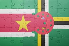 Puzzle with the national flag of dominica and suriname. Concept royalty free stock photography