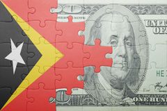 Puzzle with the national flag of east timor and dollar banknote Royalty Free Stock Image