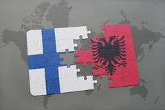 Puzzle with the national flag of finland and albania on a world map background. Stock Photography