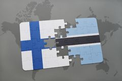 Puzzle with the national flag of finland and botswana on a world map background. 3D illustration Stock Photos