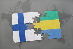 Puzzle with the national flag of finland and gabon on a world map background. 3D illustration Stock Image