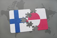 Puzzle with the national flag of finland and greenland on a world map background. Stock Images