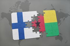 Puzzle with the national flag of finland and guinea bissau on a world map background. Stock Photo