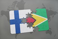 Puzzle with the national flag of finland and guyana on a world map background. Royalty Free Stock Photography