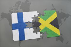 Puzzle with the national flag of finland and jamaica on a world map background. Royalty Free Stock Photography