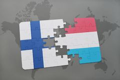 Puzzle with the national flag of finland and luxembourg on a world map background. 3D illustration Stock Photos