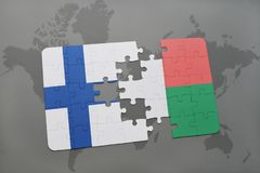 Puzzle with the national flag of finland and madagascar on a world map background. 3D illustration Royalty Free Stock Photo