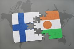 Puzzle with the national flag of finland and niger on a world map background. Stock Photos