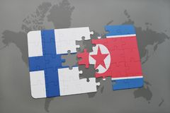 Puzzle with the national flag of finland and north korea on a world map background. Royalty Free Stock Image