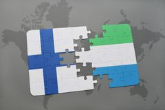 Puzzle with the national flag of finland and sierra leone on a world map background. Royalty Free Stock Photography