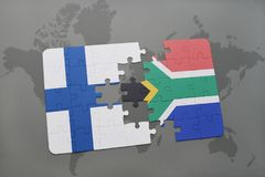 Puzzle with the national flag of finland and south africa on a world map background. Royalty Free Stock Images