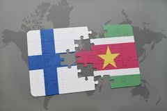 Puzzle with the national flag of finland and suriname on a world map background. Stock Image