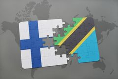 Puzzle with the national flag of finland and tanzania on a world map background. Stock Image