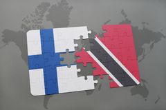 Puzzle with the national flag of finland and trinidad and tobago on a world map background. Royalty Free Stock Images