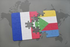 puzzle with the national flag of france and comoros on a world map background. Royalty Free Stock Image