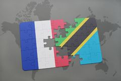 puzzle with the national flag of france and tanzania on a world map background. Royalty Free Stock Photo