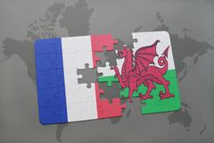 Puzzle with the national flag of france and wales on a world map background. 3D illustration Royalty Free Stock Image