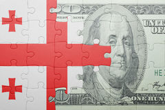 Puzzle with the national flag of georgia and dollar banknote. Concept Stock Image