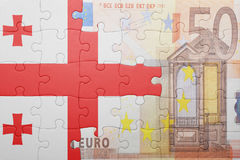 Puzzle with the national flag of georgia and euro banknote Stock Photos