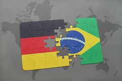 Puzzle with the national flag of germany and brazil on a world map background. 3D illustration stock photo