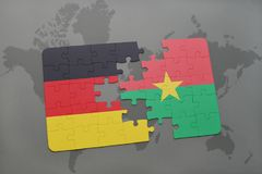 Puzzle with the national flag of germany and burkina faso on a world map background. 3D illustration royalty free stock photography