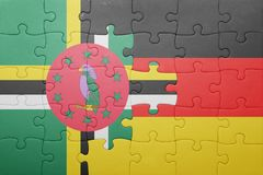 Puzzle with the national flag of germany and dominica. Concept stock image